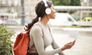 Canva Shallow Focus Photo of Woman Holding Smartphone While Listening to Music